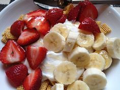 chex cereal topped with non-fat apple cinnamon greek yogurt, banana and strawberry slices, and honey
