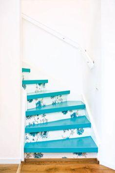 escada com degrau em azul turquesa e espelho do degrau com estampa floral