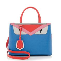 This petite Fendi tote is a miniature version of the iconic 2Jours design. It is made from royal blue saffiano leather with monster eye appliques and trimmings in bright orange and light pink leather. Details include silver-tone hardware, a framed silhouette, two rolled top handles, and a snap closure. The interior is fully lined with one zippered pocket. Carry this style on the forearm, over the shoulder, or cross body.