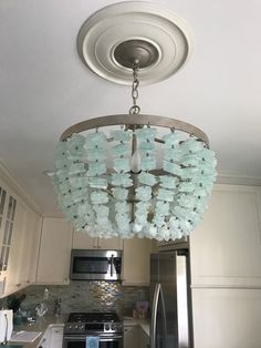 here it is with what looks like possibly glass tile backsplash Sea Glass Chandelier, Hudson Lighting, Rustic Lake Houses, Beach House Kitchens, Sea Glass, Coastal Light Fixtures, Home Decor Lights, Chandelier, Coastal Pendant Lighting