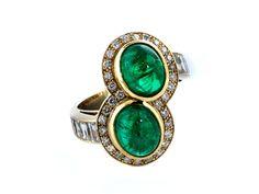 Ringweite: 53. Ringkopflänge: ca. 2,3 cm. Breite: ca. 2 cm. Gewicht: ca. 9,7 g. GG 750. Außergewöhnlicher Zwillingsring mit Smaragdcabochons, zus. ca. 5 ct,...