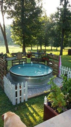 So beautiful stock tank pool area decorated with white fences and wooden pallet planters.