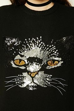 A wool-blend sweater featuring a sequined cat face, a round neckline, dropped long sleeves, and ribbed trim.