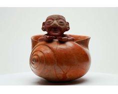 Anciano emergiendo del caracol. La pieza muestra a un anciano, posiblemente la personificación del dios N asociado con los b'akab'o'ob' y los pawahtuno'ob', emergiendo de un caracol. Para los mayas los caracoles representaban la tierra, el inframundo y la muerte, pero de igual forma eran símbolos de vida, nacimiento y agua, ligados con la feminidad al igual que con los atributos de la diosa lunar como numen de la procreación de la tierra y el agua.