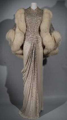 Norman Hartnell, 1960. Silk Jersey, embroidered and encrusted with rhinestones. The matching jacket is trimmed in fox fur. From the collection of the Fashion Museum in Bath, UK.