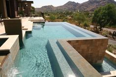 Overlooking a magnificent desert panorama, this 70-foot-long infinity pool with a spa sits at the front of the house, where from the street level it appears to be a simple water feature. Finished in Hydrazzo with travertine coping, the pool also features tile in three different colors and sizes. HydroScapes, LLC, Fountain Hills, Arizona