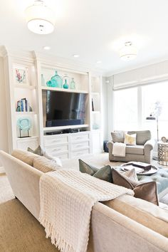 Living room with pops of color. New 2017 interior design trend, neutral rooms with pops of color. living-room-media-cabinet-with-turquoise-decor #popsofcolor #neutralinteriors #2017interiortrends