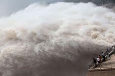 Gente observando un caudal extraordinario de agua en la represa de Xialangdi , en la región central de China. Inundaciones que se estan produciendo desde fines de Junio ya han causado la muerte de 295 personas, el colapso de edificios y deslizamientos de tierras. (AFP)