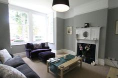 Beautiful lounge in Victorian house with grey walls, stunning sash windows and original fireplace
