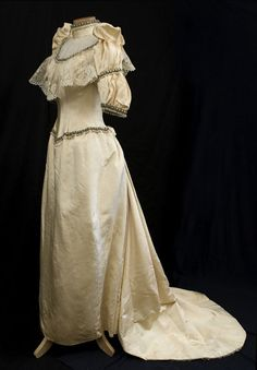 1883 wedding gown made from cream-colored silk faille, the gown is finely embellished with a matching chiffon neckline insert, bands of crystal beads and faux pearls, and a wide bodice flounce of handmade Brussels lace. The exaggerated puffed sleeve caps and sweeping back train add drama to the design.