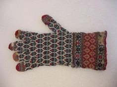 probably 19 c. Gloves. Knit wool. Dimensions: 4 5/16 x 6 5/16 in. (11 x 16 cm). Identified as from Persia by the museum, but have much more in common with Kasmir/ Indian patterns. White ground with all-over pattern of stylized flowers in green, black, & red with red finger tips, and three wrist borders, the outer two with conventional vine scrolls and the inner with angular yellow design on red ground. Gloves are mended in many places and torn in many more. Brooklyn Museum.