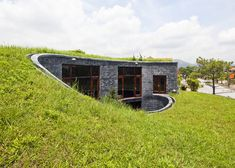 This spiralling stone house in Vietnam by architect Vo Trong Nghia has grass on its roof and an oval courtyard at its centre.