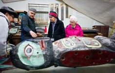 Haines Tlingit carver Wayne Price tells elders Rosa Miller, center, Kaayistaan Marie Olson, right, and John Morris about his work to restore the Big Dipper Totem at the U.S. Forest Service woodshop on Wednesday.   Michael Penn | Juneau Empire