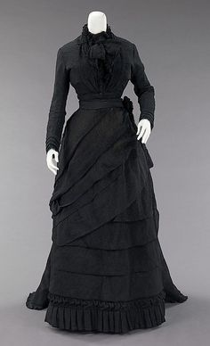Mourning clothing tended to follow the fashionable silhouette of the period, much like this exquisitely finished full mourning dress. This dress shows typical high style 1870s touches such as asymmetry, the bustle back and decorative hem details. The refined details are worked in black crinkled crepe, a common textile used for mourning attire, which indicates that the owner may have had the garment produced for a special occasion.