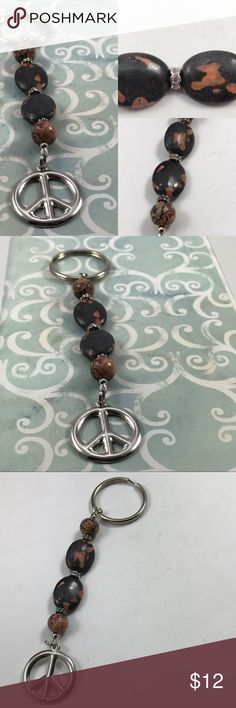 Peace Sign Key Ring Peace sign key ring. Has 2 larger stones in brown mixed color and 2 round stones brown mixed color. There are small silver pieces between each stone.  Key ring on one side and the peace sign on the other side. New hand made item. Hand Made Accessories Key & Card Holders