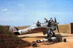 """A Hawker Typhoon Mark IB (s/n """"HH-N"""") """"Dirty Dora"""", of No 175 Squadron, Royal Air Force, undergoing servicing in a blast-walled dispersal point at Colerne. Two dummy bombs for practice loading on to the wing racks can be seen in the foreground. Aircraft Photos, Ww2 Aircraft, Fighter Aircraft, Military Aircraft, Fighter Jets, Luftwaffe, Image Avion, Hawker Tempest, Hawker Typhoon"""