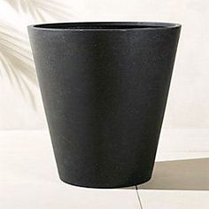 Modern faux-stone planter is handmade from an innovative polystone material that resembles natural stone—both in looks and durability. Modern conical shape and black finish accent any decor.