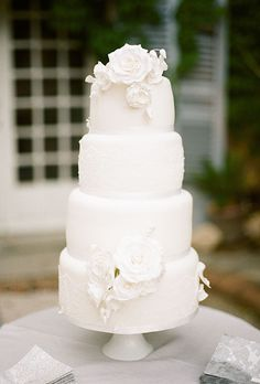 A four-tiered white wedding cake with sugar flowers