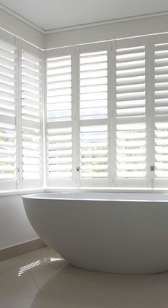 Free standing bath, love the white shutters they give privacy and light at the same time