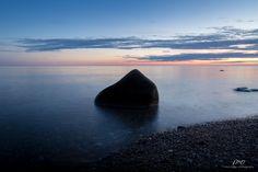 A photograph of calm seas and silhouetted rock at dusk along the beach near Baker's Brook near Rocky Harbour, NL inside Gros Morne National Park.