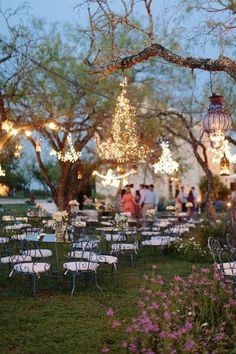 Whimsical / fairytale wedding set outside with tables and chairs and twinkling lights surrounded by nature and watched by the moon.