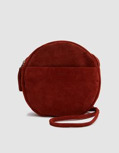 Shoulder bag from Baggu in Rust. Suede. Long thin strap. Top zip closure. Exterior pocket. Four interior slot pockets. Tonal embossed logo. Lined. • Leather • Spot clean