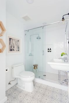 """""""Here you can see how we used a teak bathroom stool to mix with the chrome shower head to have that nice pop. I also love how different the artwork is. The piece by Rubin 415 called 'Ode to New York (Fawn)' caught my eye because it's not something you often see in spaces."""""""