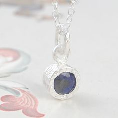 Simple, elegant and full of class, this sterling silver solitaire necklace features hand-faceted midnight blue precious sapphire set into a gently textured surround. #Embersjewellery #Jewellery #Sapphire#Women