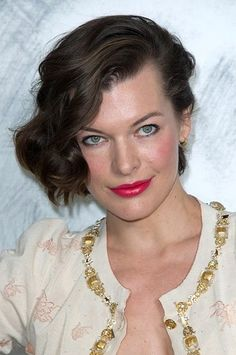 Milla Jovovich's bright pink lips and side swept hair look feminine and elegant.