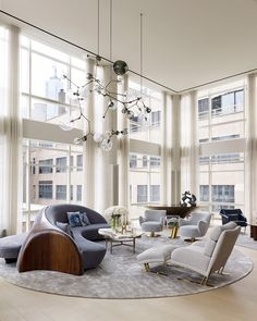Tribeca Triplex designed by Amy Lau. Photo by Bjorn Wallander. Chandelier by Lindsey Adelman; swivel chairs and custom sofa by Vladimir Kagan; low table by Silas Seandel; carpet by Fort Street Studio. Photo courtesy of Amy Lau.