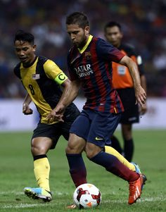 Jordi Alba of Barcelona FC is tackled by Safiq Rahimi of Malaysia during the friendly match between FC Barcelona and Malaysia at the Shah Alam Stadium on August 10, 2013 in Kuala Lumpur, Malaysia.