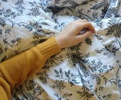 a photo of someone wearing a yellow sweater's hand against a floral-patterned bedspread