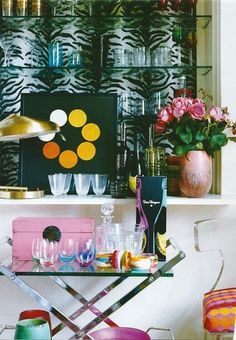 this space feels lieka party! zebra mirrors, pink, orange, yellow, lucite chair, flowers and a great side table as a bar cart - love it!