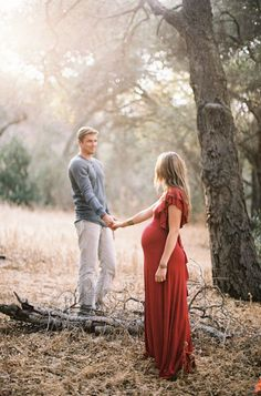 Forest Maternity Session, red dress, couple, hand holding, sunlight, branches, gray shirt