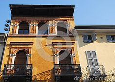 Photo made in two homes in Lodi in Lombardy (Italy). In the picture you see the upper part of two very different homes aesthetically. The house on the left highest is yellow and has two large balconies with massive wrought iron railing. Under the big roof pitch you see three large windows. The left light color has left a small balcony with a railing smaller and slender.