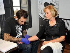 Vero López y el tatuador del evento.