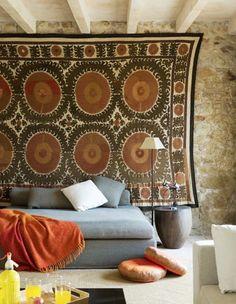 suzani on stone wall with grey sofa <3, via chic & deco