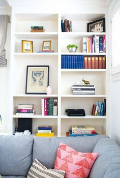Colorful bookshelf with colorful books and decorative elements like plants, vintage typewriters and frames
