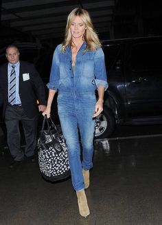 """Heidi Klum Photos Photos - """"America's Got Talent"""" judge Heidi Klum wore a denim jumper as she arrived at LAX airport to catch a red eye flight on December 3, 2014 in Los Angeles, California. Earlier in the day, the 41-year-old model tweeted about her donation of $25,000 to a local charity. """"Happy to be at the @ChildrensLA tree lighting and present this check for #HelpingHands Fund."""" - Heidi Klum Catches a Flight"""