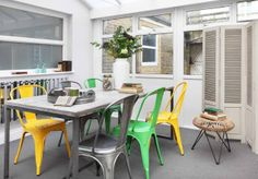 The conservatory is a bright and airy space, filled with natural light and embellished with citrus colours. Industrial-style Tolix A chairs in yellow, green and stainless steel sit around a table made from reclaimed wood and raw steel