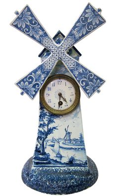Dutch windmill clock is sculpted from pottery & hand designed with the traditional blue & white Delft colors. The clock is hand painted including a wonderful panel beneath its face depicting a charming Dutch rural scene.