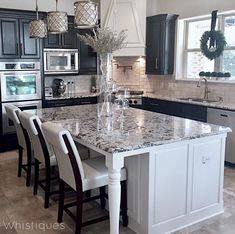Dark cabinets, light island, backsplash