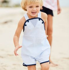 Little ones will look ship shape wearing this nautical romper. Comfortable straps cross in back and button in front. Sizes 3-24m feature snap closure at leg. 100% cotton; machine wash. Seersucker Stripe available in Blue or Red with Navy trim. Sizes 3m-3y. *bella bliss® uses the finest cottons available. For best results, lay flat to dry then fluff on low heat.