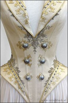 """By Royal Black -- """"The Admiral"""" is a uniform inspired corset top with high collar, lapels, spiky epaulets and semi-transparent detachable skirt pieces. / The corset is made from satin and is elaborately decorated with lace applique, synthetic leather cut work, silver beads, Swarovski crystals and metal buttons. The epaulets are made from sturdy thermoplast and are also decorated with beads, Swarovski crystals and buttons."""