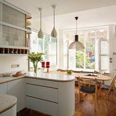 This small kitchen was extended to make it open plan with the dining room giving the space a lighter larger feel. The curved edges of the ktichen create a friendly relaxed vibe which is mirrored with the curves of the dining table. The retro kitchen mimics 30s style with the glass cabinets heralding from the 60s and again adding to a more lightfilled kitchen. http://www.housetohome.co.uk/kitchen/picture/modern-kitchen-with-oak-flooring-and-curvaceous-peninsula
