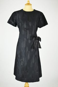This stylish and collectible vintage wiggle dress is by classic brand Horrockses Fashions, and is made of black crimplene with bow and button detail to the hip. Wiggle Dress, 1960s, Short Sleeve Dresses, Bows, Buttons, Shirt Dress, Detail, Stylish, Classic
