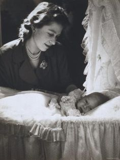 Princess Elizabeth, later Queen Elizabeth II, watches over her first born, Prince Charles.