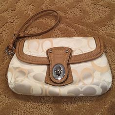 Coach wristlet Coach wristlet. Cream and tan. In good condition- no signs of wear except pull is missing a part ( see pic) . Still very useable. Latch with front packet and zipper pocket. Size approx. 7.5 x 4.5 excluding handle. Coach Bags Clutches & Wristlets