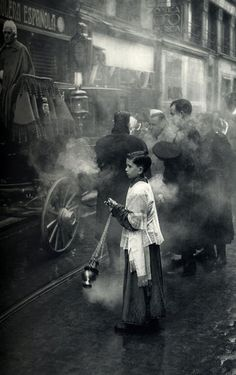 Henri Cartier-Bresson. SPAIN. Madrid. 1953. The priest steps up to bring the Blessed Sacrament to an ill person during a procession, accompanied by military music near the Puerta del Sol.