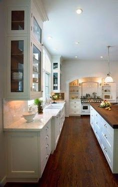White cabinets, marble counters, farmhouse sink, and a dark stained wood floor.